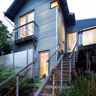 Diseño de fachada de piso gris, urbana, pequeña, de dos plantas, con revestimiento de metal y tejado a dos aguas