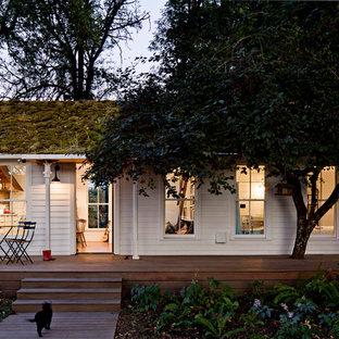 Immagine della facciata di una casa piccola bianca country a un piano con rivestimento in legno e copertura verde