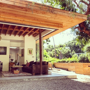 Inspiration for a small eclectic beige two-story glass exterior home remodel in Los Angeles with a mixed material roof