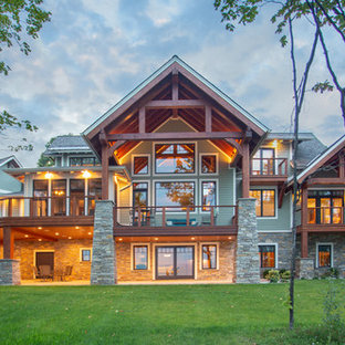 Large craftsman green three-story mixed siding gable roof idea in Other with a mixed material roof