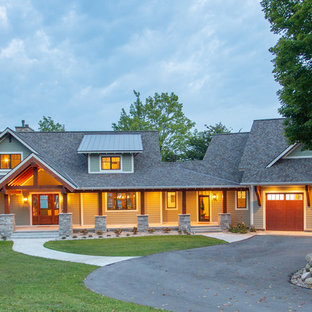 Large craftsman green two-story metal exterior home idea in Other with a mixed material roof