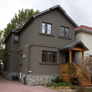 Mid-sized modern gray two-story stucco gable roof idea in Toronto
