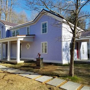 Foto della facciata di una casa unifamiliare grande viola classica a due piani con rivestimento in legno, tetto a capanna e copertura in metallo o lamiera