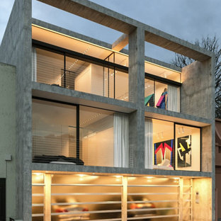 Photo of a mid-sized industrial concrete grey townhouse exterior in Melbourne with three or more storeys, a flat roof and a mixed roof.