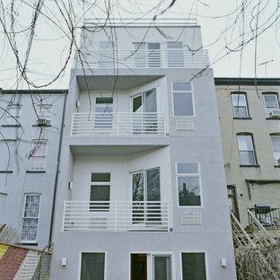 ニューヨークの中くらいのトラディショナルスタイルのおしゃれな家の外観 (漆喰サイディング、グレーの外壁、タウンハウス) の写真