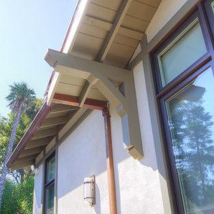 Diseño de fachada de casa blanca, bohemia, de tamaño medio, de una planta, con revestimiento de estuco, tejado a dos aguas y tejado de teja de madera