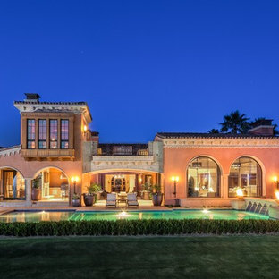 Photo of a mediterranean two-storey stucco pink exterior in Orange County.