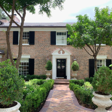 Traditional Brick Classic Home with White Trim and Black Shutters