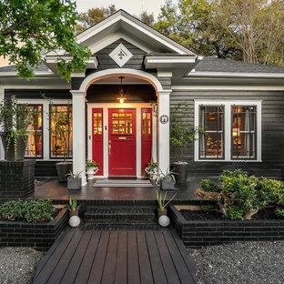 Foto de fachada de casa negra, clásica, de una planta, con revestimiento de madera