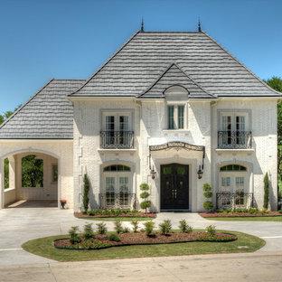 Diseño de fachada blanca, clásica, de dos plantas, con revestimiento de ladrillo y tejado a cuatro aguas