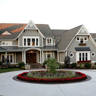 Imagen de fachada gris, clásica, de dos plantas, con revestimiento de madera y tejado de varios materiales