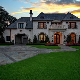Elegant beige two-story stone house exterior photo in Dallas with a hip roof and a shingle roof