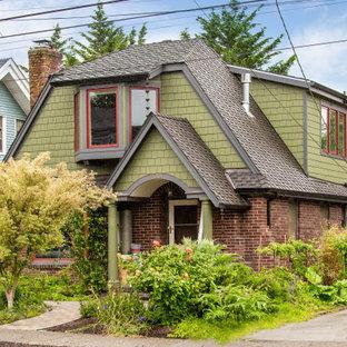 Exempel på ett klassiskt grönt hus, med två våningar och tak i shingel