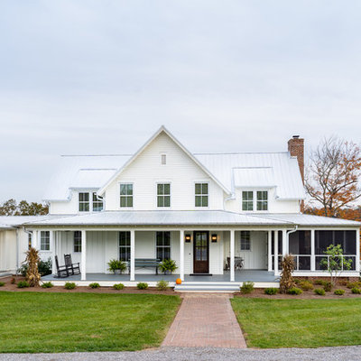 Large farmhouse white three-story concrete fiberboard exterior home idea in Other with a metal roof