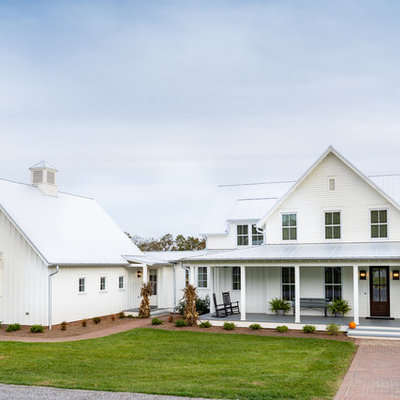 Inspiration for a large farmhouse white three-story concrete fiberboard exterior home remodel in Other with a metal roof