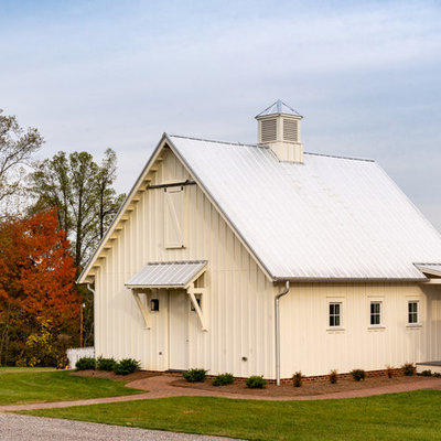 Large cottage white three-story concrete fiberboard exterior home photo in Other with a metal roof