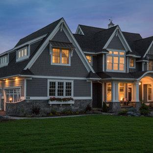 Foto de fachada de casa gris, clásica, extra grande, de dos plantas, con revestimiento de aglomerado de cemento, tejado a dos aguas y tejado de teja de madera
