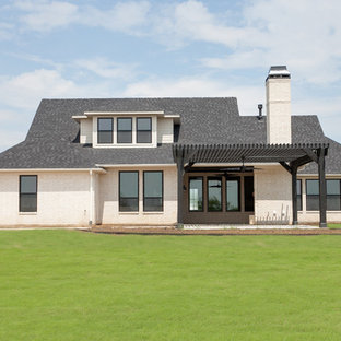 Large minimalist white two-story brick house exterior photo in Dallas with a clipped gable roof and a shingle roof