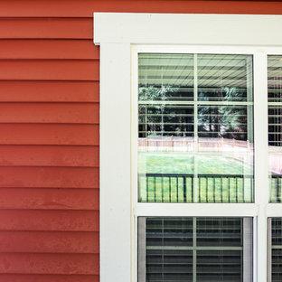 バンクーバーの小さいトラディショナルスタイルのおしゃれな家の外観 (ビニールサイディング、赤い外壁) の写真