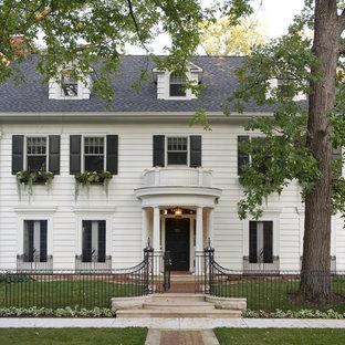 Exemple d'une façade en bois blanche chic à deux étages et plus avec un toit à deux pans.