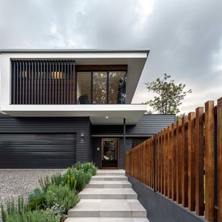 Contemporary two-storey black house exterior in Brisbane with mixed siding and a flat roof.