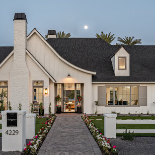 Example of a farmhouse white one-story house exterior design in Phoenix with a hip roof and a shingle roof