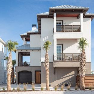 Diseño de fachada de casa blanca, costera, grande, de tres plantas, con revestimiento de estuco, tejado a cuatro aguas y tejado de metal