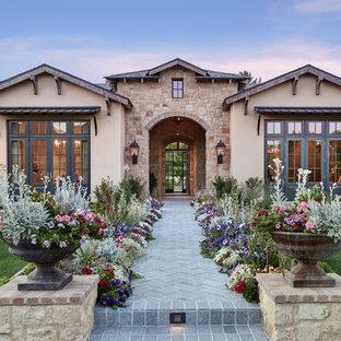 Ispirazione per la facciata di una casa unifamiliare grande beige mediterranea a un piano con rivestimenti misti, tetto a capanna e copertura a scandole