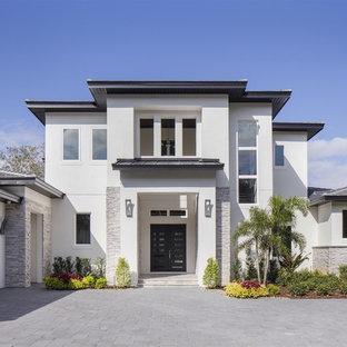 Imagen de fachada de casa blanca, minimalista, grande, de dos plantas, con revestimiento de estuco, tejado a dos aguas y tejado de teja de barro