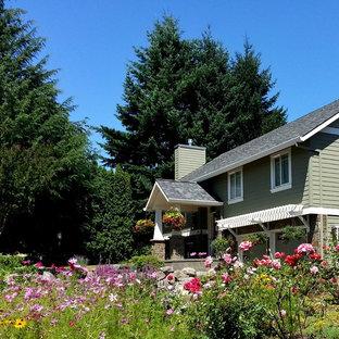Diseño de fachada de casa verde, tradicional renovada, grande, a niveles, con tejado a dos aguas, revestimientos combinados y tejado de teja de madera