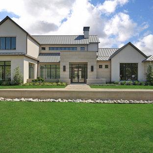 Esempio della facciata di una casa unifamiliare beige classica a due piani con rivestimenti misti, tetto a capanna e copertura in metallo o lamiera