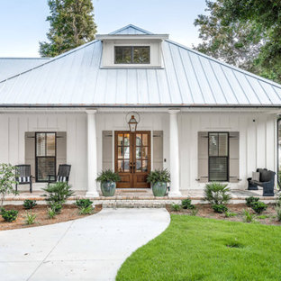 Large traditional white two-story concrete fiberboard exterior home idea with a metal roof