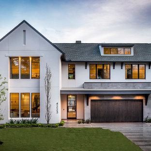 Foto della facciata di una casa unifamiliare grande bianca classica a due piani con rivestimento in stucco, tetto a capanna e copertura a scandole