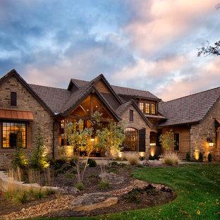 На фото: большой, коричневый дом в стиле рустика с разными уровнями, облицовкой из камня и двускатной крышей с