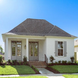 Example of a mid-sized minimalist white one-story brick exterior home design in New Orleans with a clipped gable roof