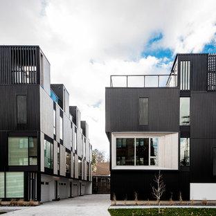Foto de fachada de piso negra, minimalista, de tamaño medio, de tres plantas, con revestimiento de metal, tejado plano y tejado de metal