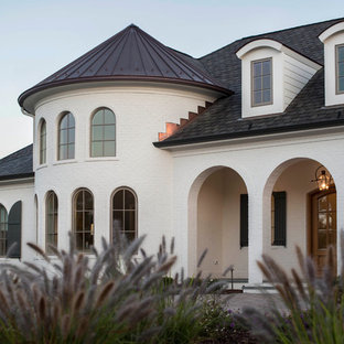 Inspiration for a large eclectic white two-story brick house exterior remodel in Raleigh with a hip roof and a mixed material roof