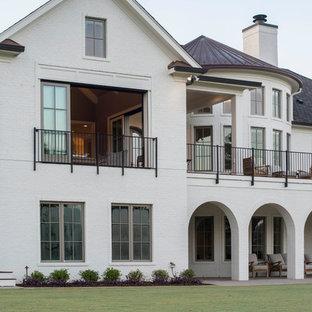 Imagen de fachada de casa blanca, bohemia, grande, de dos plantas, con revestimiento de ladrillo, tejado a cuatro aguas y tejado de varios materiales