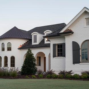 Ejemplo de fachada de casa blanca, ecléctica, grande, de dos plantas, con revestimiento de ladrillo, tejado a cuatro aguas y tejado de varios materiales
