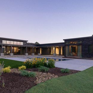 Ejemplo de fachada de casa marrón, moderna, extra grande, de una planta, con revestimiento de madera
