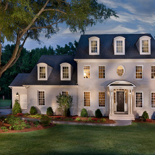 Example of a large classic white three-story brick exterior home design in Charlotte