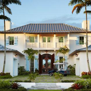 Imagen de fachada beige, tropical, de dos plantas, con tejado a cuatro aguas