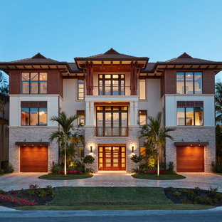Inspiration for a mid-sized tropical multicolored three-story mixed siding house exterior remodel in Miami with a hip roof and a shingle roof