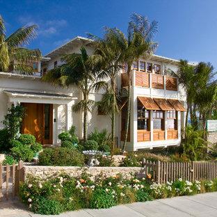 Exemple d'une façade de maison blanche exotique à un étage avec un revêtement en stuc et un toit plat.