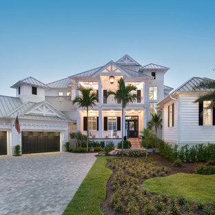 Exempel på ett exotiskt vitt hus, med två våningar, valmat tak och tak i metall