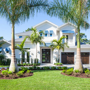 Island style white two-story exterior home photo in Miami