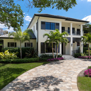 Large island style white two-story stucco exterior home photo in Miami with a hip roof