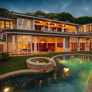 Inspiration for a large tropical beige two-story wood exterior home remodel in Hawaii