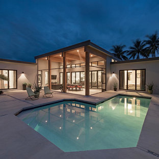 Design ideas for a mid-sized modern one-storey stucco grey exterior in Miami with a flat roof.