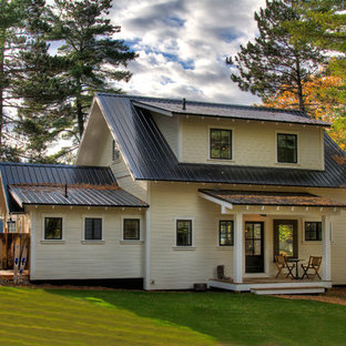 Mountain style beige two-story exterior home photo in Minneapolis with a metal roof